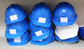 Lots of blue and one white construction helmets are on shelves Royalty Free Stock Photography