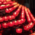Lots of burning red candles in a church