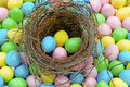 Lots of candy Easter Eggs surround a bird's nest. Royalty Free Stock Images