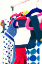 Lots of colorful dresses on hangers in shop Royalty Free Stock Photos
