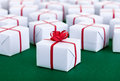 Lots of presents in white gift boxes on green surface with red ribbons Royalty Free Stock Photos