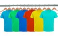 Lots of T-shirts on hangers isolated on white Royalty Free Stock Photo