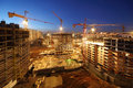 Lots of tower cranes build large residential buildings at night Royalty Free Stock Photo