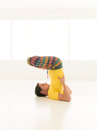 Lotus in head colorful dressed male repeating the yoga exercises a white room with window background Stock Image