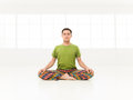 Lotus position studio young man doing yoga in white window Royalty Free Stock Photos