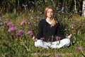Lotus yoga pose woman meditating in the city park at summer morning beautiful blue flowers in foreground Stock Images