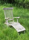 Lounge chair in wildly grown field of grass. Royalty Free Stock Photo