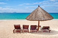 Loungers and straw umbrella on a tropical beach Royalty Free Stock Image