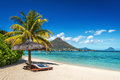 Loungers and umbrella on tropical beach in Mauritius Royalty Free Stock Photo