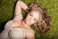 Lounging in the grass a pretty caucasian girl with thick blond curly hair resting with her hand behind her back on green of park Royalty Free Stock Photography