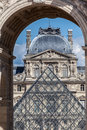 Louvre museum paris france an arch at the historical and the glass structure of the pyramid Stock Images