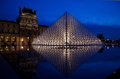 The louvre museum paris in night scene with illuminated pyramid and blue sky Royalty Free Stock Photos