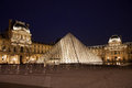 Louvre museum paris with pyramid in by night with lights on Royalty Free Stock Photo