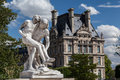 Louvre paris a marble statue of a man holding an ill person in the tuileries garden and one of the towers of the museum france Stock Image