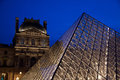 Louvre in paris museum by night with illuminated pyramid and blue sky Stock Image
