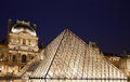 Louvre paris museum with pyramid in by night with lights on Royalty Free Stock Image