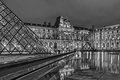 Louvre and pyramids long exposed black and white night photo.