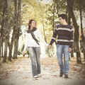 Love and affection between a young couple at the park in autumn season selective focus with shallow dof Stock Photos