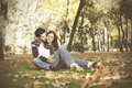 Love and affection between a young couple at the park in autumn season selective focus with shallow dof Royalty Free Stock Photos
