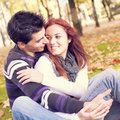 Love and affection between a young couple at the park in autumn season selective focus with shallow dof Royalty Free Stock Photo