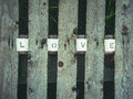 Love being spelled the letters that creates the word is arranged between planks Royalty Free Stock Photo