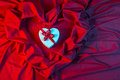 Love card with heart on a red fabric white ribbon in blue light Royalty Free Stock Photo
