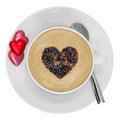 Love coffee cup of cappuccino with a heart sprinkle on top and heart shaped chocolates on the side isolated on white background Royalty Free Stock Photography