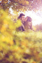Love couple embrace under a tree in the autumn park Royalty Free Stock Photo