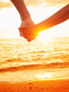 Love couple holding hands in love beach sunset at romantic young lovers walking by the sea romance close up of women and men Stock Photo