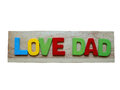Love dad. Happy Father Day celebrations. Love dad word from colorful of wood on wooden background isolate on white background. Royalty Free Stock Photo