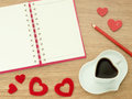 Love diary. Valentines day background with heart shape of cup with coffee, red hearts, book for diary and color pencils on wood fl Royalty Free Stock Photo