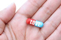 Love dose hand holding a capsule labeled Royalty Free Stock Photos