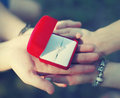 Love engagement and wedding concept hands couple holding ring a box with a closeup Royalty Free Stock Image