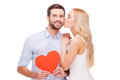 Love is a great feeling beautiful young loving couple bonding to each other while women kissing her boyfriend holding red heart Royalty Free Stock Photo