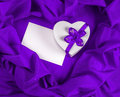 Love greeting card with heart on a purple fabric white and ribbon Royalty Free Stock Photo