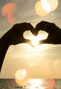 Love hands making heart shape in summertime with sun flares Royalty Free Stock Image