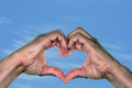 Love and hands in the shape of a heart against blue sky on warm day Royalty Free Stock Image