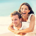 Love happy couple on beach having fun piggyback ride outdoor smiling laughing together romantic holidays vacation travel Royalty Free Stock Photo