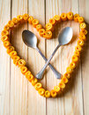 Love heart from orange peels with crossed spoons sign twisted inside on a wooden background Royalty Free Stock Photos