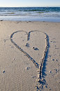 Love heart in the sand with background yacht. Royalty Free Stock Photo