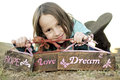 Love hope and dream girl holding three stenciled wooden weathered barn wood signs that say Stock Photos