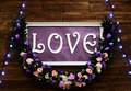 Love inscription on a wooden background, flashing lights and flowers. Decorative artistic animation devoted to the Royalty Free Stock Photo