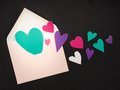 Love letter real cut out of paper hearts coming out of an envelope for your romantic copy Royalty Free Stock Image