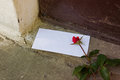 Love letter and red rose in vase in front of doorway concept Stock Images