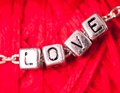 Love letters on the chain close up on red background Stock Photo