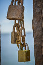 Love locks on a chain old rusty and one new hanging Stock Photography