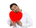 In love man closeup portrait happy smiling handsome looking upwards holding large red heart to chest daydreaming of woman isolated Stock Photos