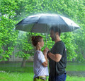 Love man and a women under an umbrella in the rain Stock Photos