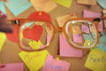 Love messages on post its seen through retro glass written colorful over a cork message board clear sight high diopter glasses Stock Image