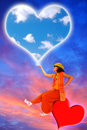 Love messenger a genie sitting on a floating heart is holding a big sky heart in its right hand Royalty Free Stock Image